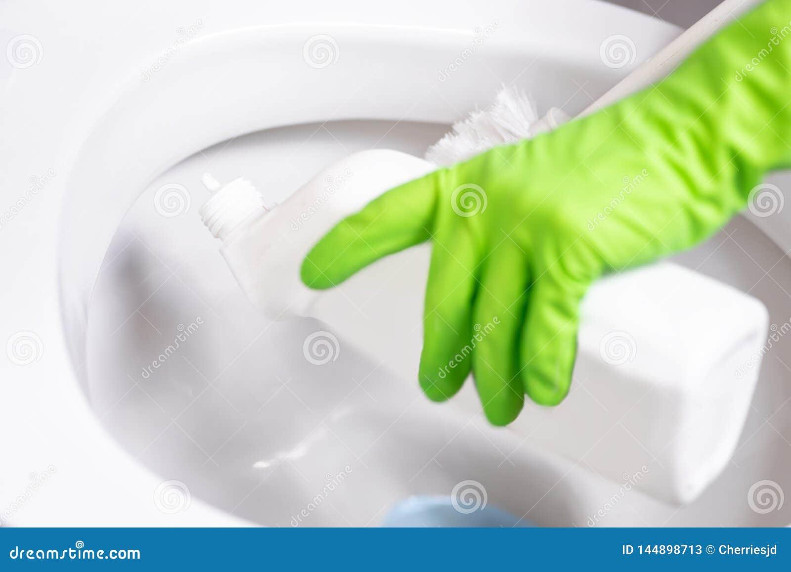 De vrouw maakt toiletkom schoon gebruikend detergens