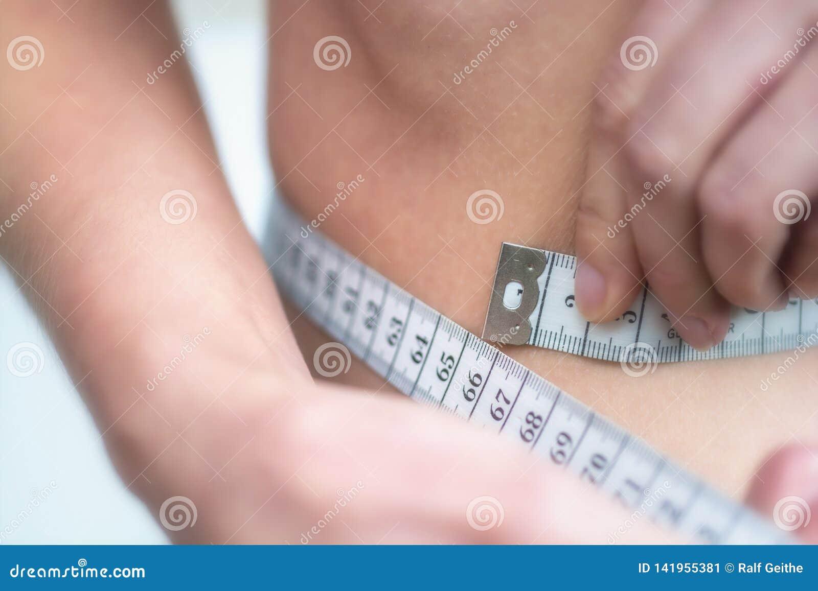 De vrouw meet zeer dunne taille met het meten van band