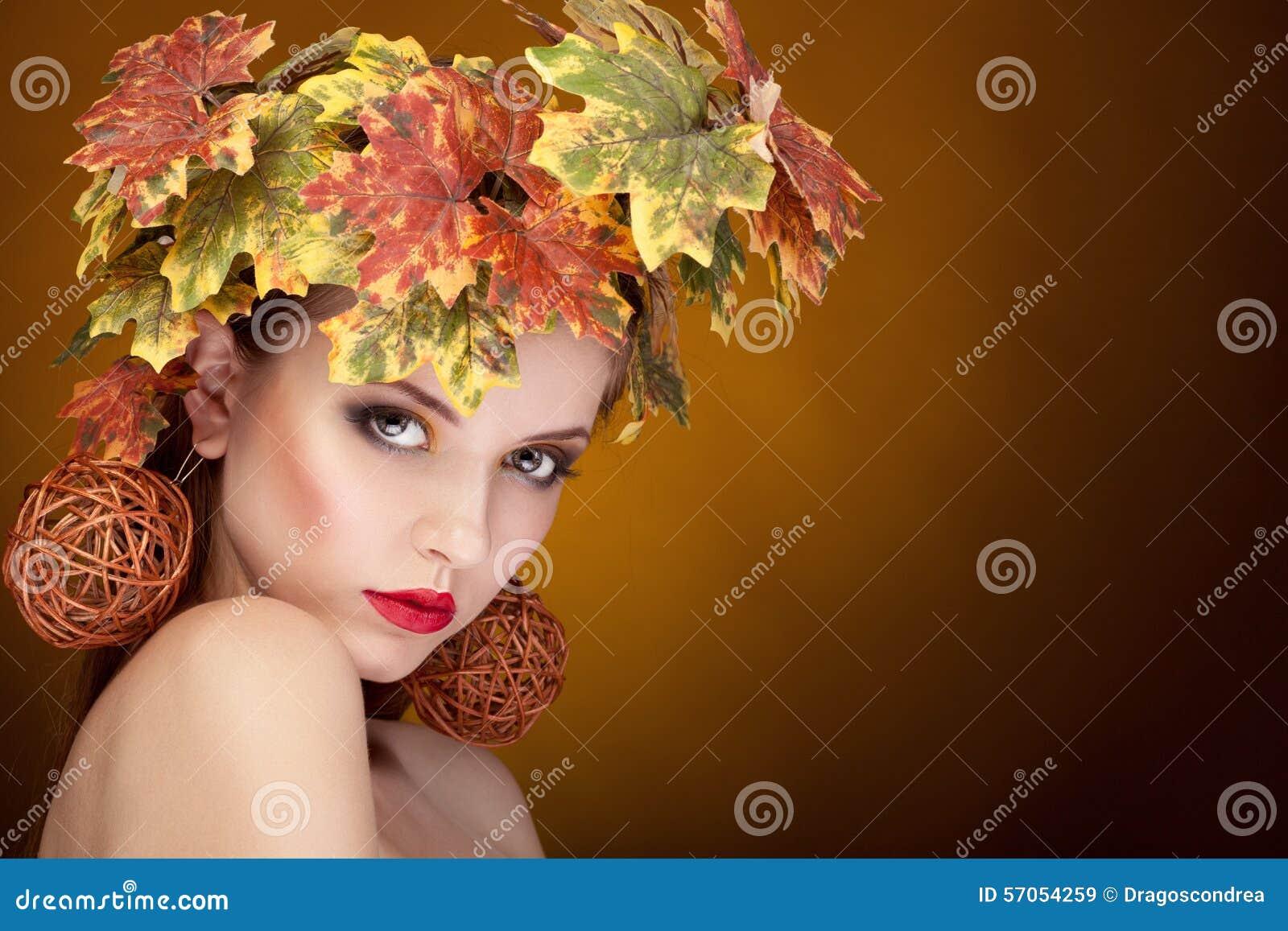 De vrouw met doorbladert op hoofd in de herfstconcept