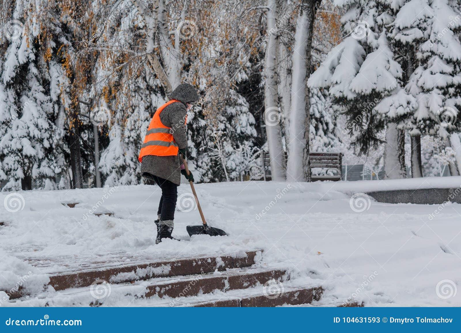 Download De Vrouw Met Een Schop In Een Oranje Vest Maakt Sneeuw Schoon Redactionele Stock Foto - Afbeelding bestaande uit december, portier: 104631593