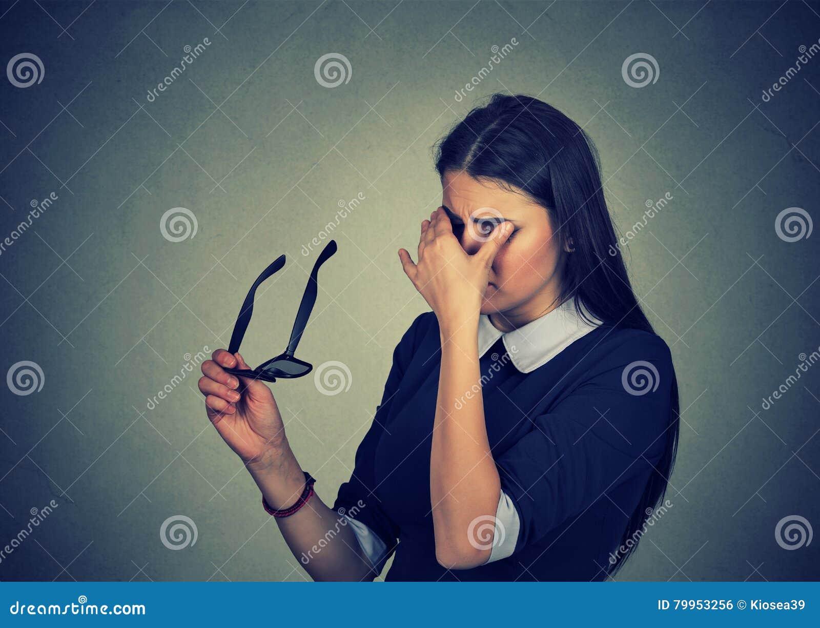 De vrouw met glazen die haar ogen wrijven voelt vermoeid