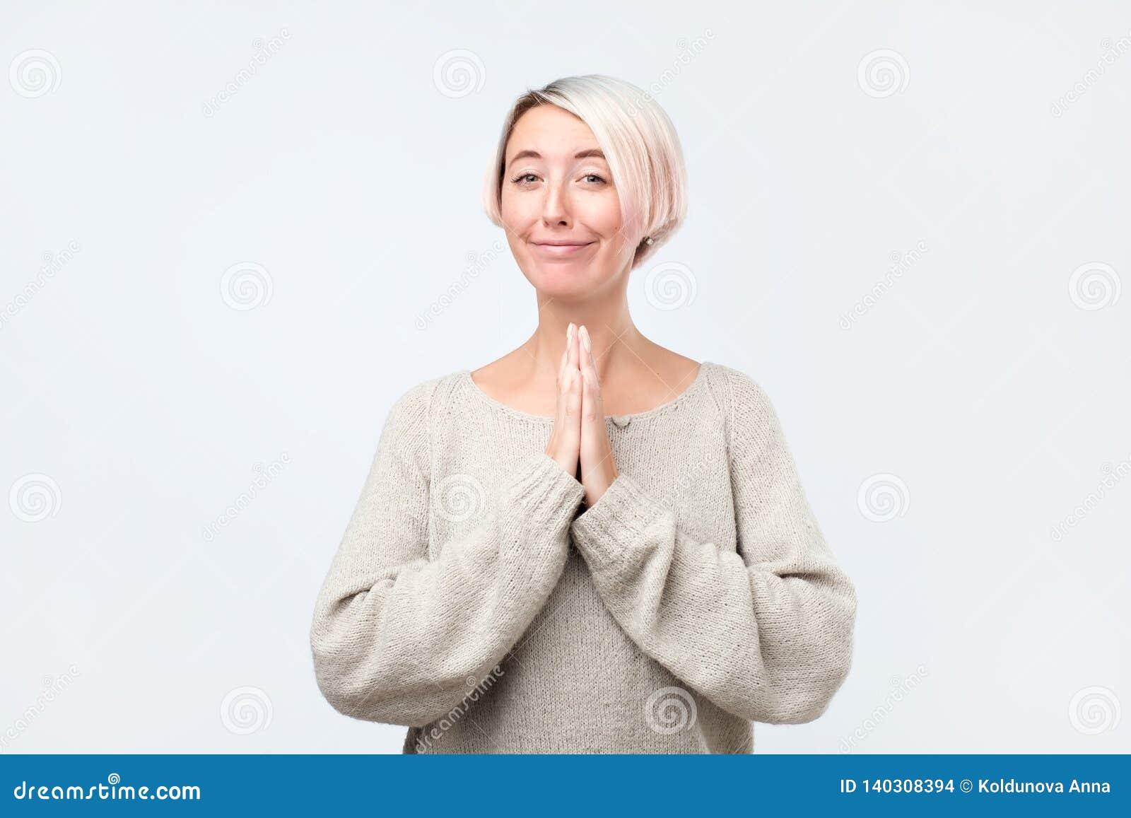 De vrouw met het een beroep doen kijkt holdingspalmen voor haar worden samengeperst, die om vergiffenis vragen die