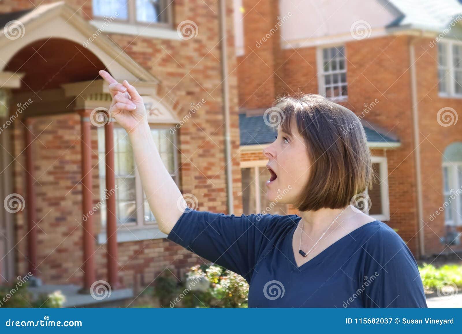 De vrouw met kort haar voor vage baksteen huisvest punten en kijkt verrast