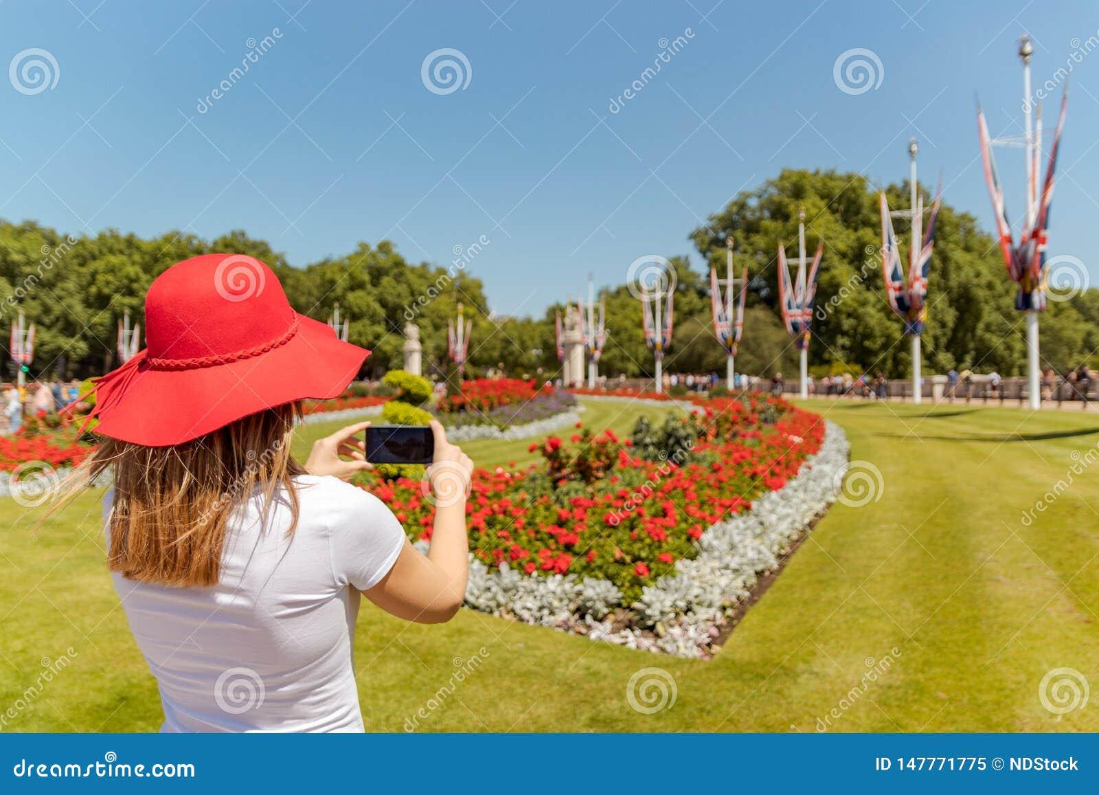 De vrouw met rode hoed neemt een beeld van bloemen met cellphone