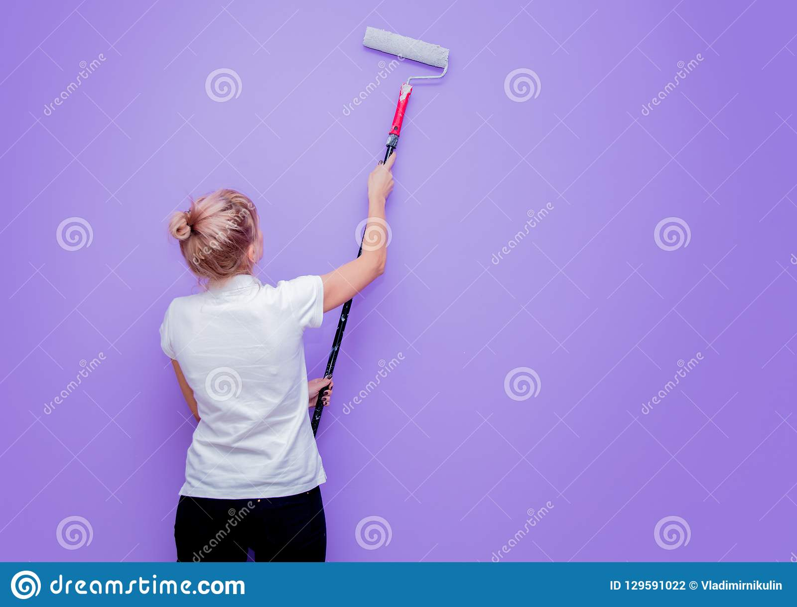 De vrouw met verfrol in eigen huis probeert aan het schilderen van een ruimte
