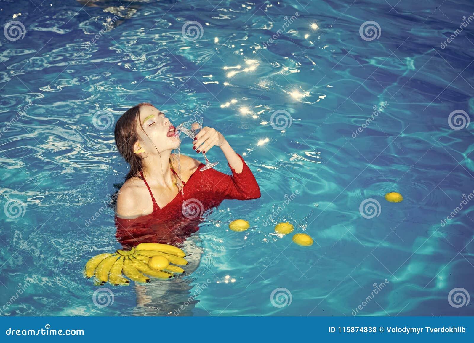 De vrouw ontspant in kuuroordpool vrouw met tropisch fruit in pool Vitamine in banaan bij meisjeszitting dichtbij water Het op di
