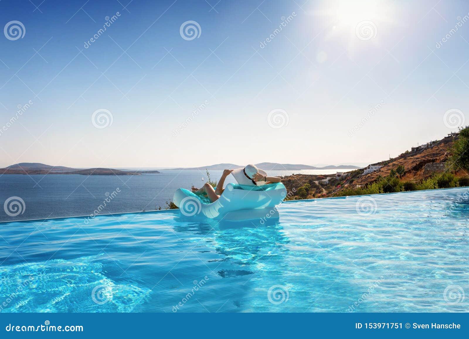 De vrouw ontspant op een vlotter onder de Mediterrane zon