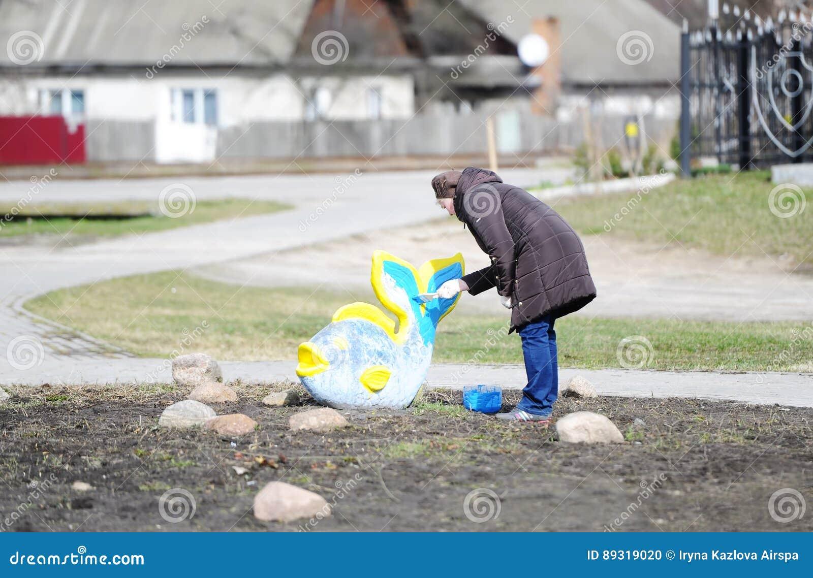 De vrouw schildert een standbeeld van vissen
