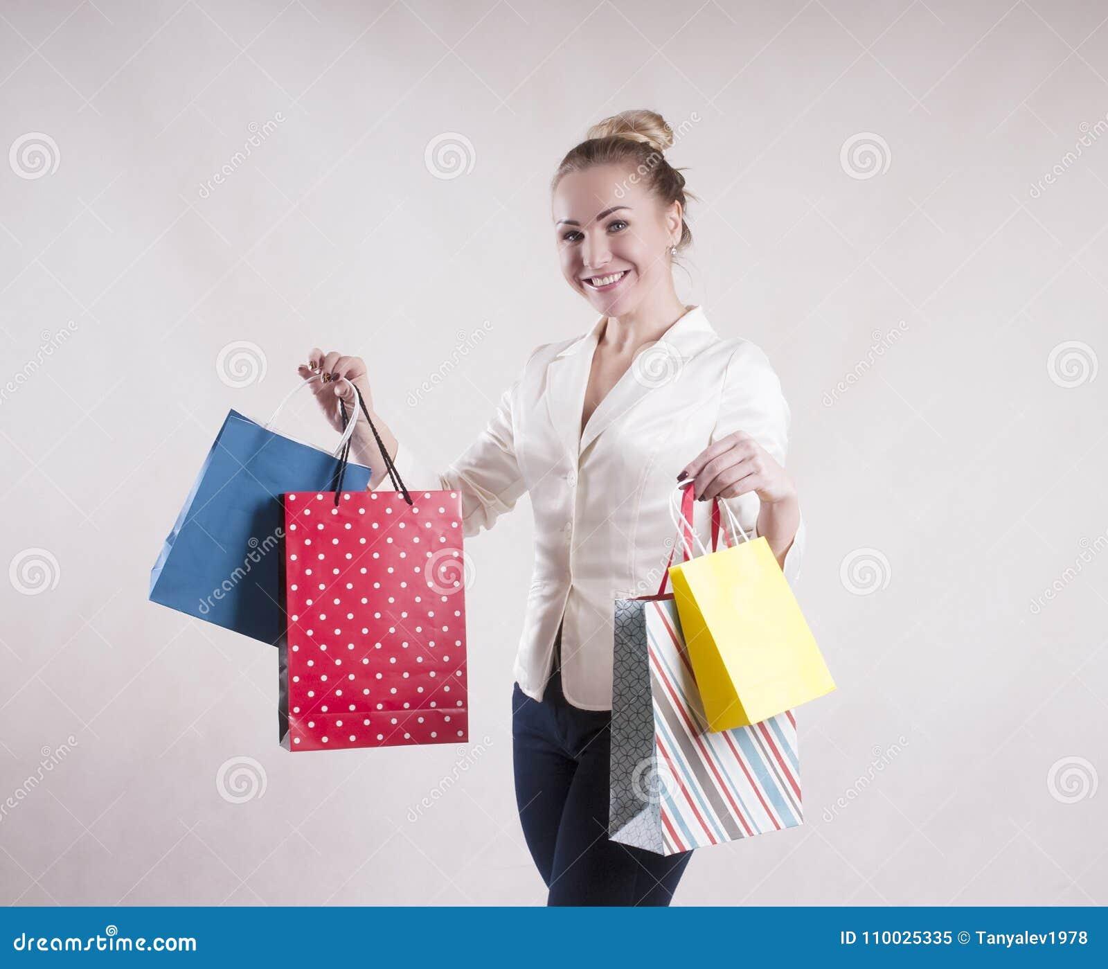 De vrouw schokte modieus een jasje in huisvrouwenpakketten voor aankopenstudio