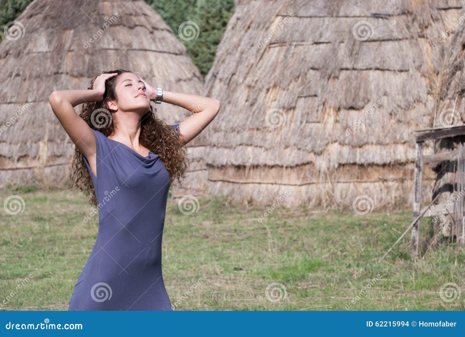 De vrouw stelt voorzijde van strohuizen