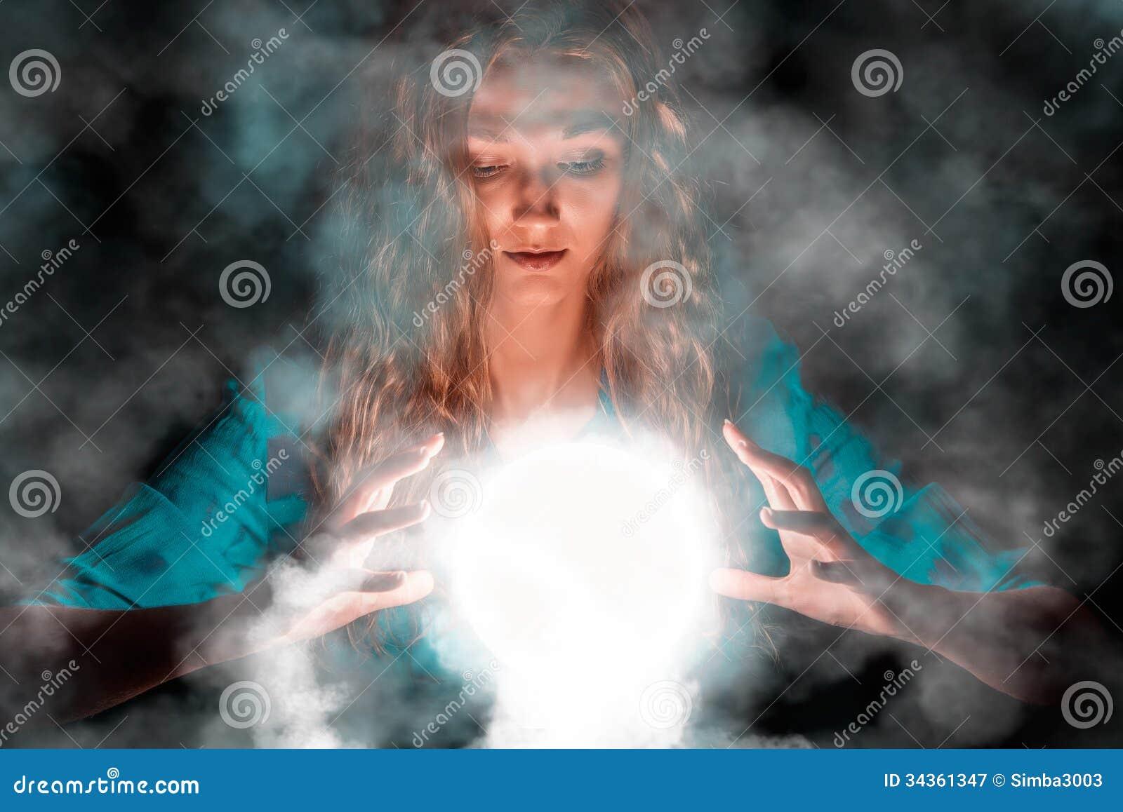 De vrouw van de fortuinteller met licht gebied in haar handen