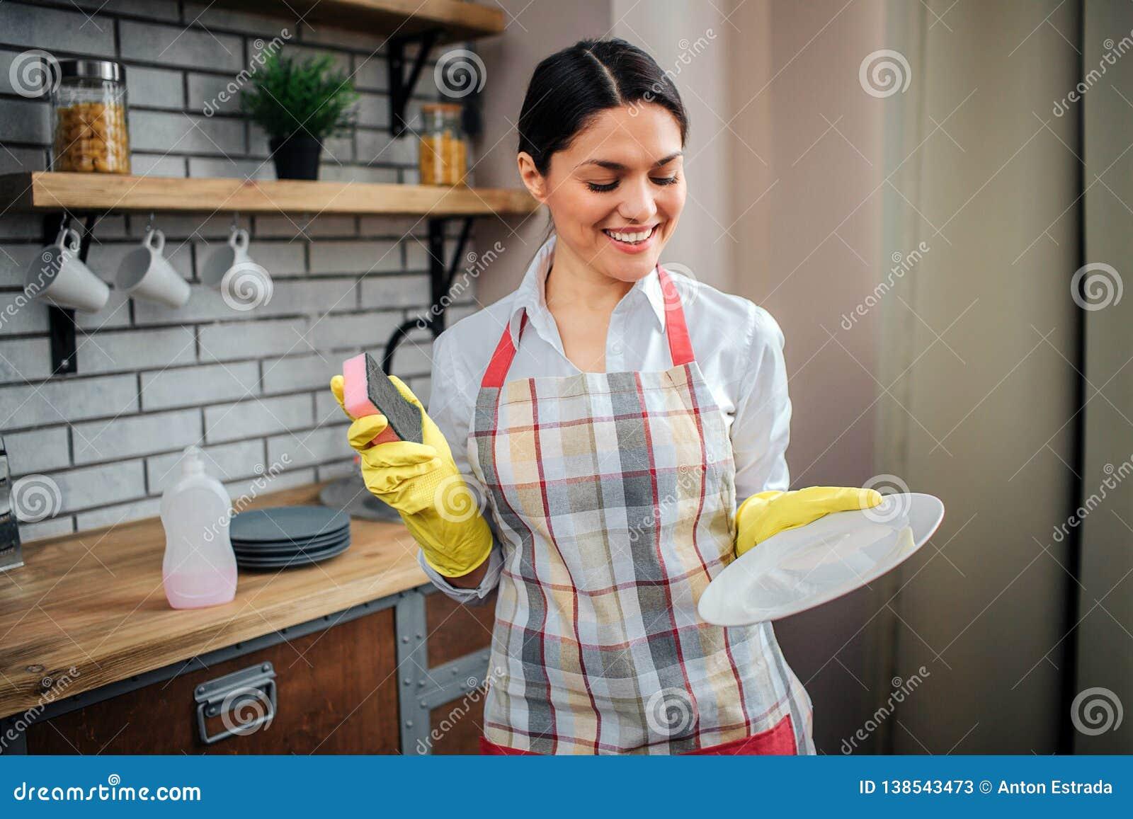 De vrouw van Nice in schorttribune in keuken en stelt Zij houdt witte plaat en glimlach Professionele vrouwelijke reinigingsmachi