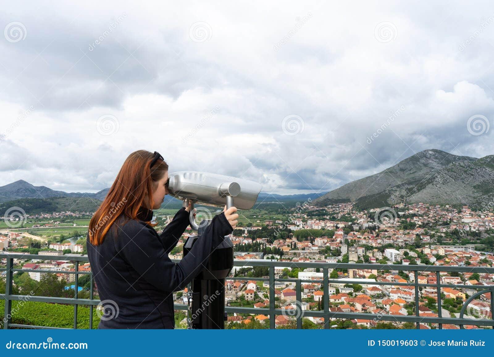 De vrouw van de reistoerist op de vakantie van Europa Het Hipstermeisje die telescoop gebruiken kijkt panorama van de stad Het re