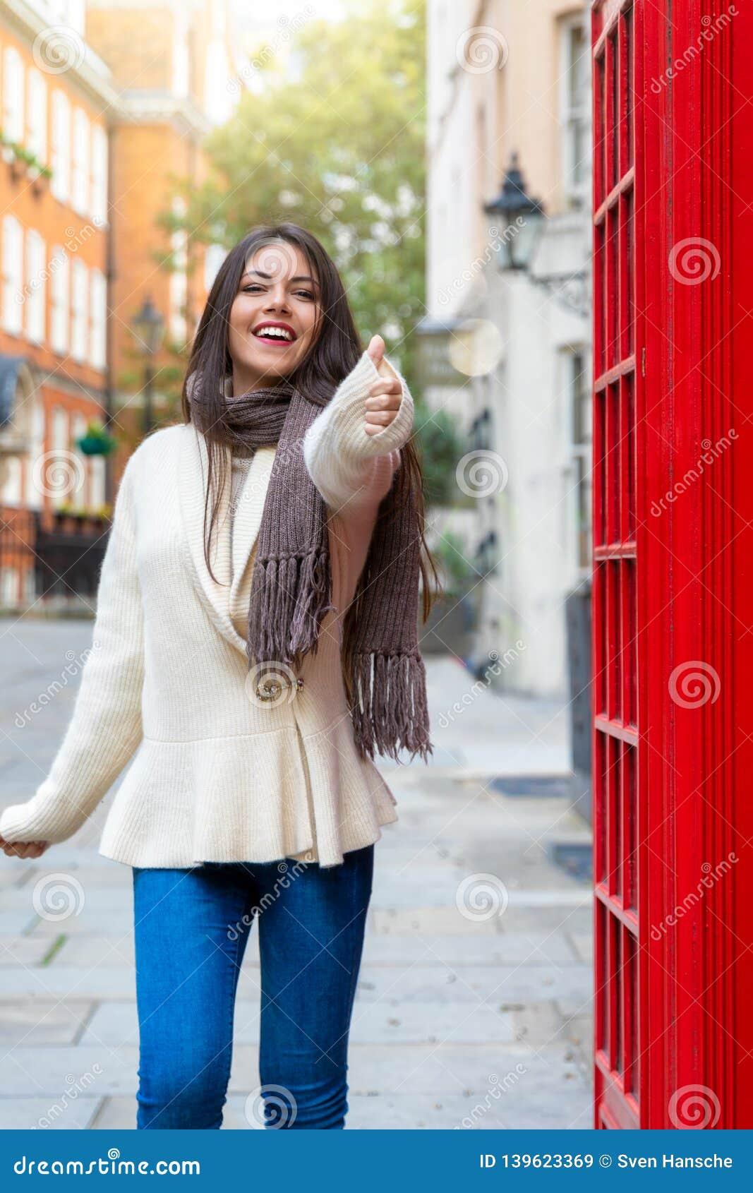 De vrouw van de stadsreiziger toont de duimen omhoog in Londen ondertekenen