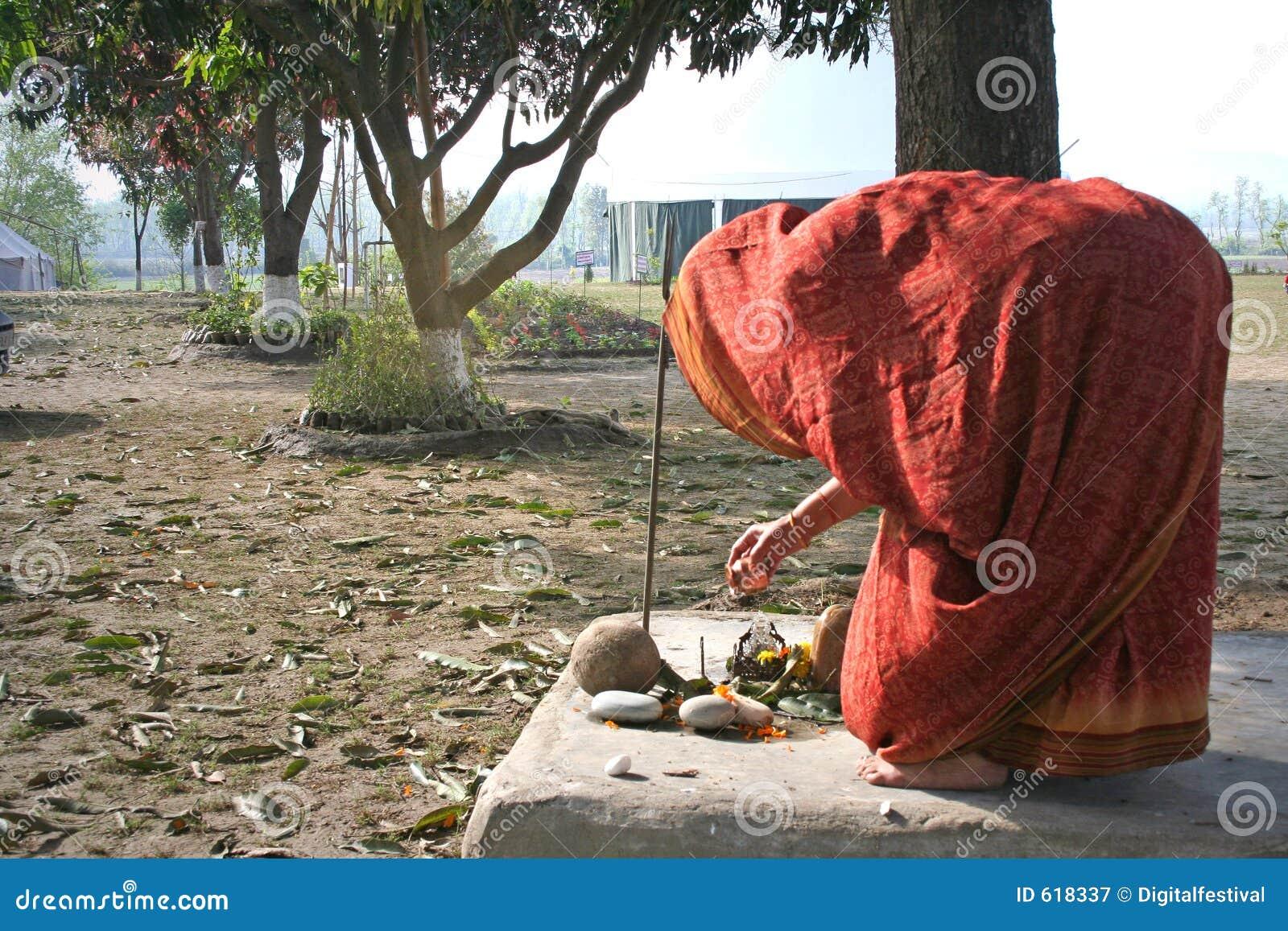 De vrouw voert het traditionele ritueel van de ochtendverering in binnenplaats uit