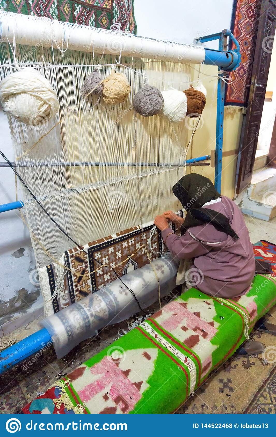 De vrouw weeft een Tapijt indient langs Kairouan, Tunesië