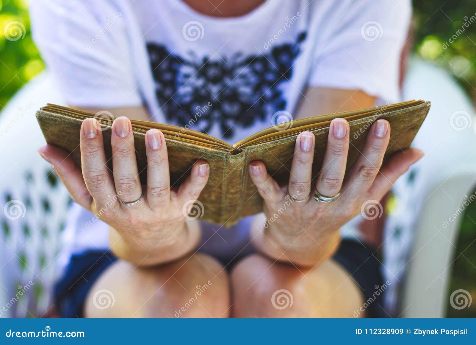 De vrouw zit als voorzitter en leest een oud boek