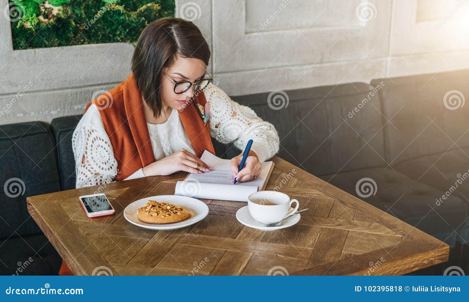 De vrouw zit in koffie bij lijst Het meisje vult een toepassing, vragenlijst, tekensdocumenten in, opstelt samenvatting