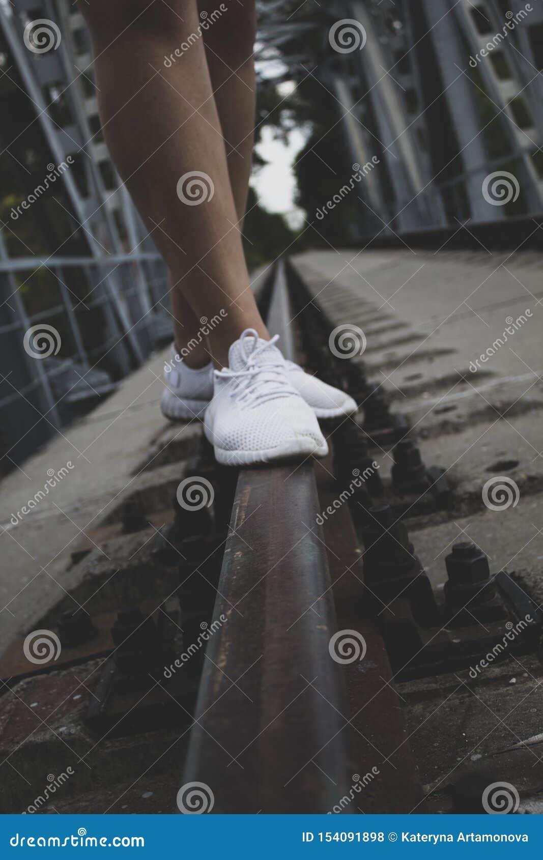 De vrouwelijke benen aan de knieën, in witte tennisschoenen, bevinden zich op de sporen