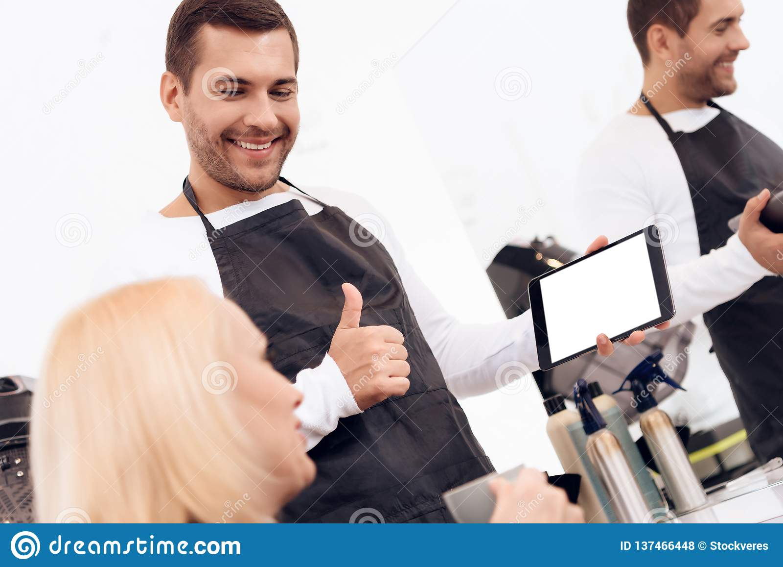 De vrouwelijke blije stilist kiest kapsel op tablet voor rijpe vrouw in schoonheidssalon