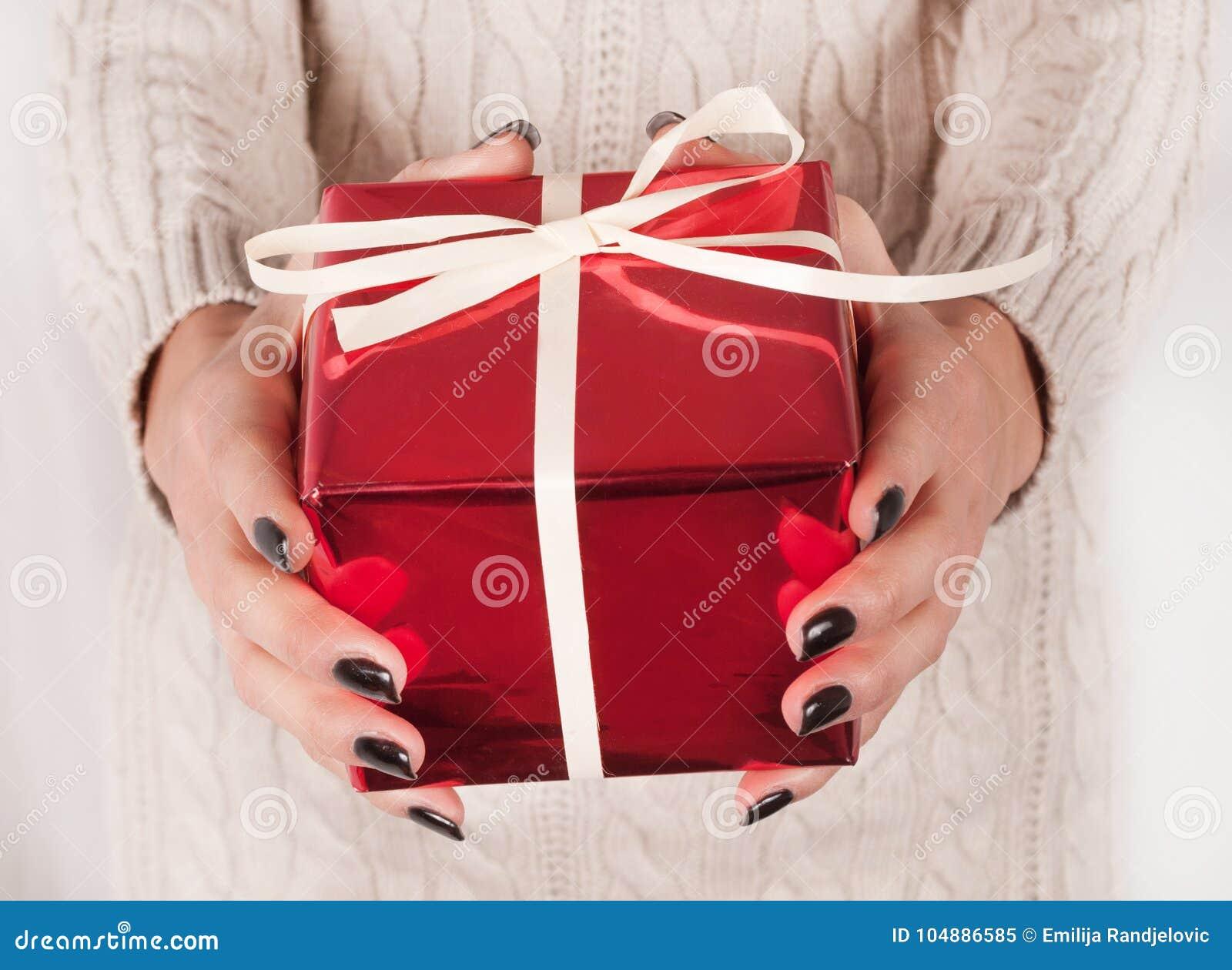 De vrouwelijke doos van de holdings rode gift in handen met zwarte spijkers en sweater