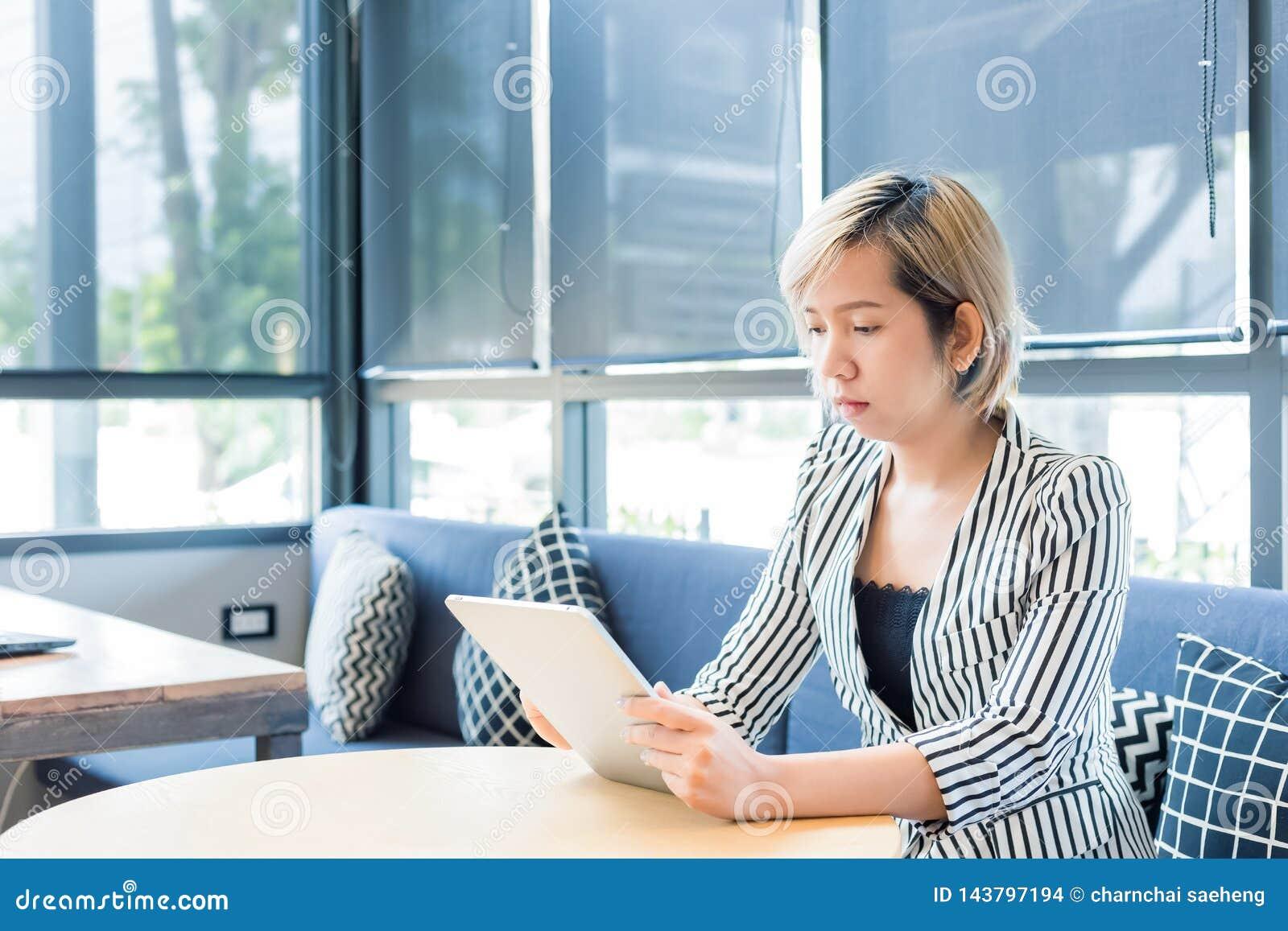 De vrouwelijke financier leest financieel nieuws in Internet via aanrakingsstootkussen tijdens het werkonderbreking in koffie De