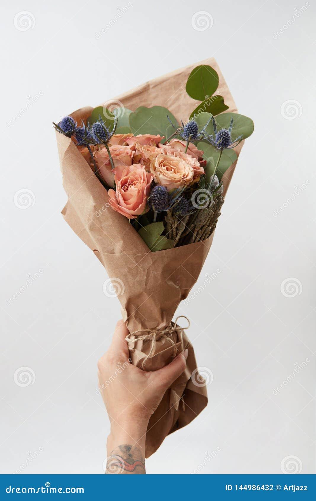 De vrouwelijke hand geeft bos met koraalrozen en groen blad op lichte achtergrond, exemplaarruimte Gift voor Moeder of van de Vro