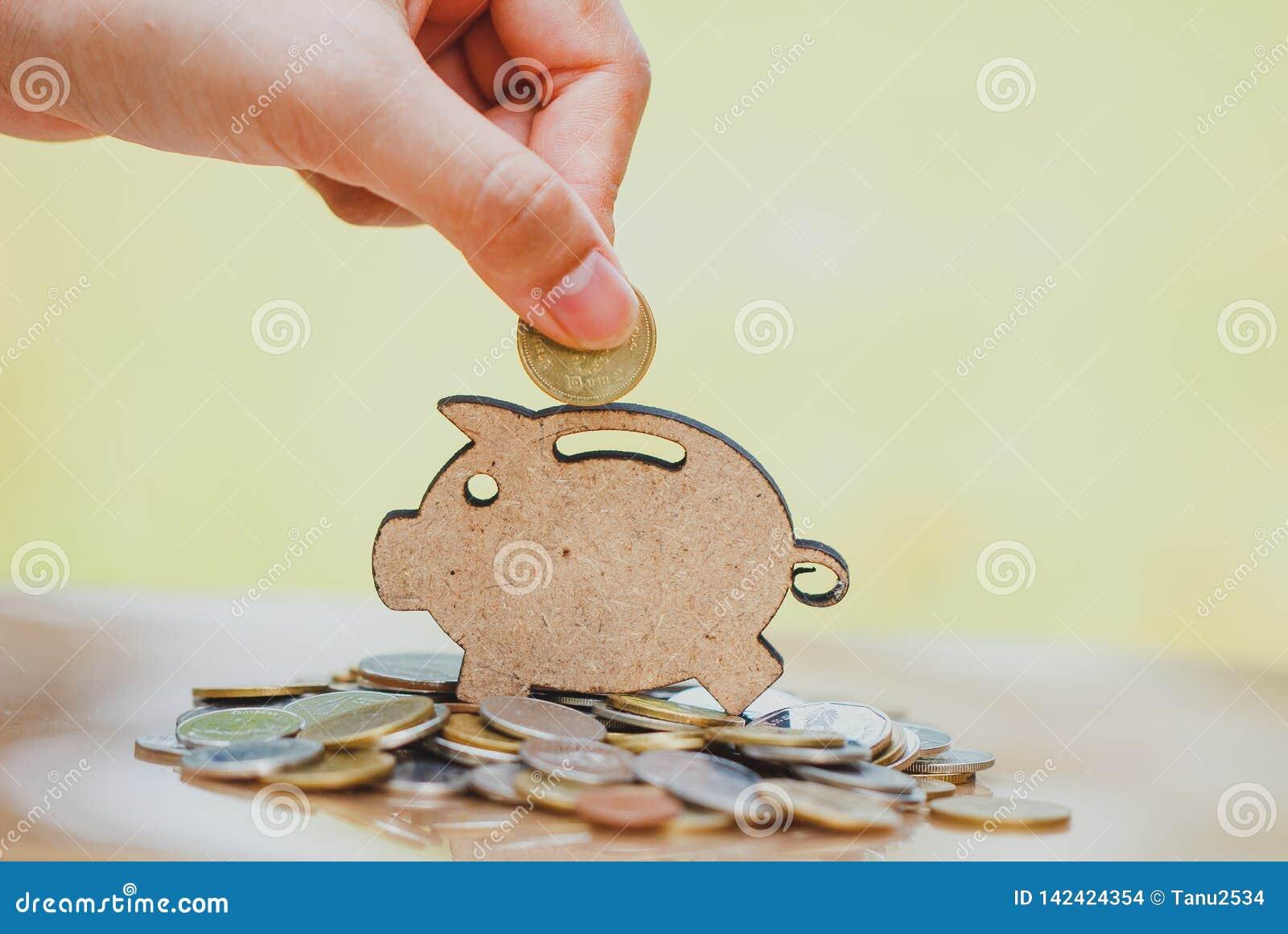 De vrouwelijke hand muntstuk zetten en de stapel die muntstukken in concept besparingen en geld het groeien of energie sparen