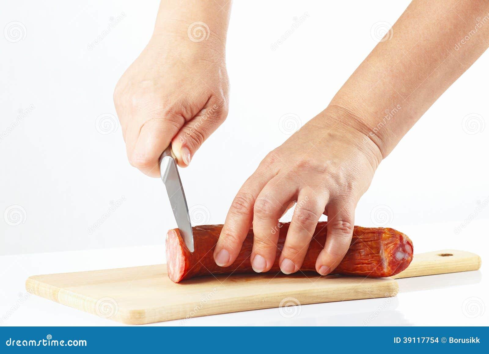 De vrouwelijke hand sneed gerookte worst