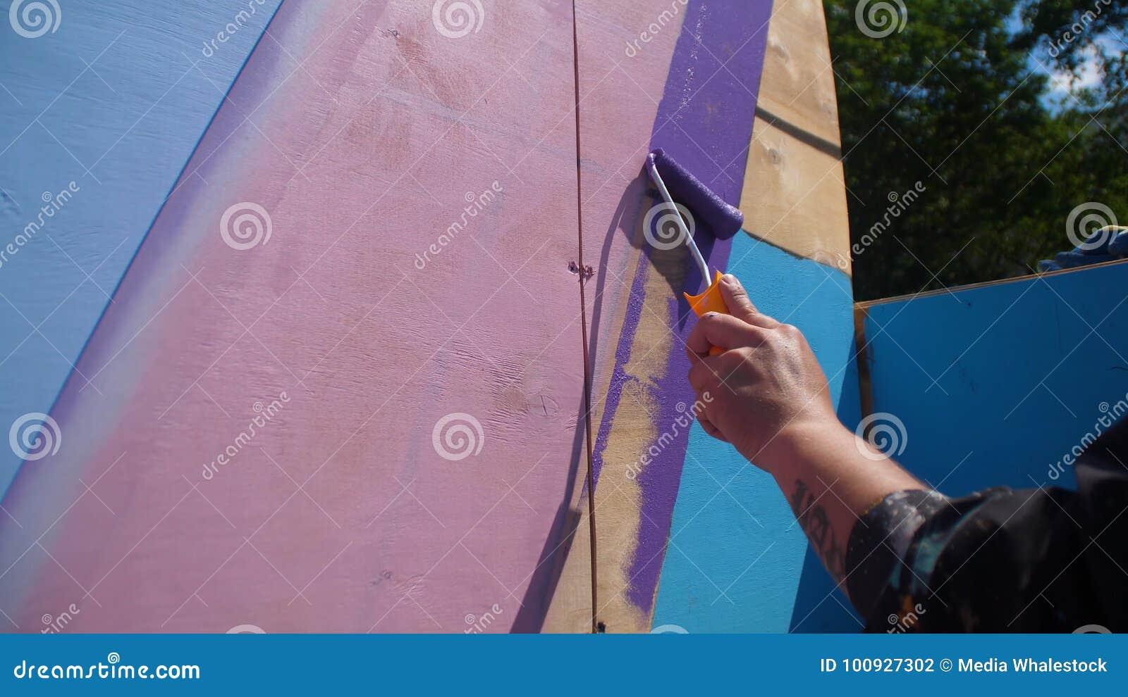 De vrouwelijke houten muur van de handverf in blauwe kleur die het schilderen rol met behulp van Het schilderen van het hout met