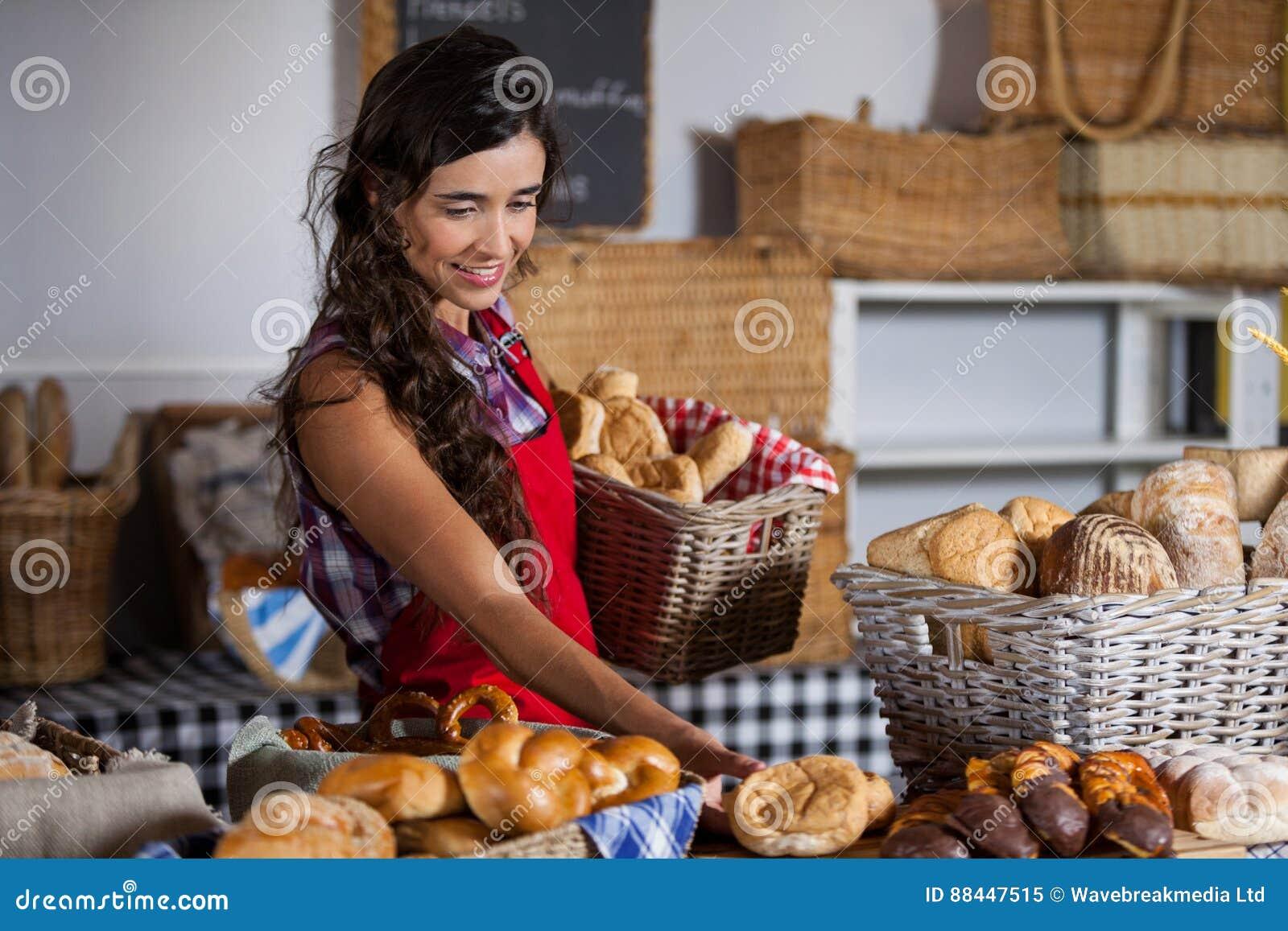 De vrouwelijke mand van de personeelsholding zoet voedsel in bakkerijsectie