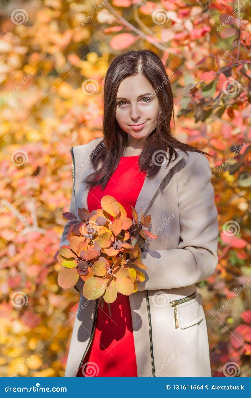 De vrouwelijke persoon met boeket van de herfst doorbladert het stellen tegen kleurrijke struiken