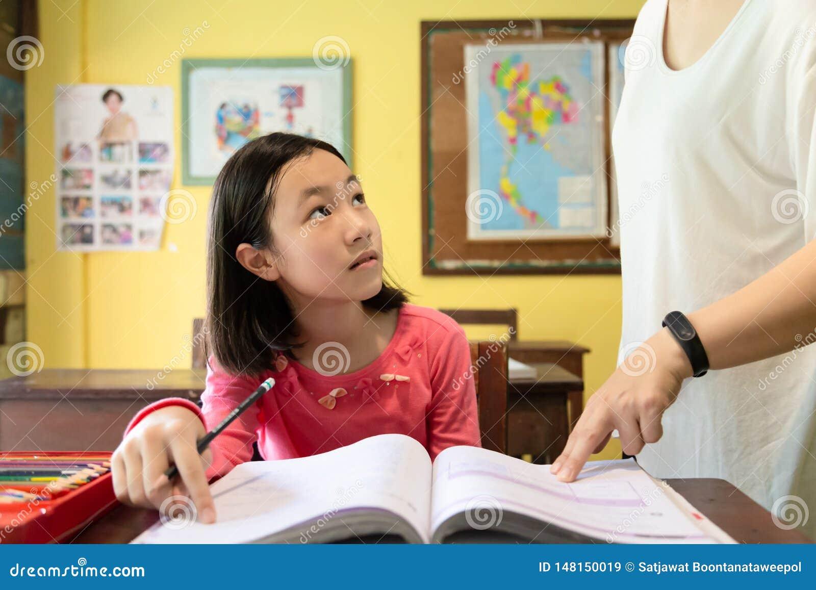 De vrouwelijke student van het leraarsonderwijs op school, leraar die meisje het bestuderen bevordert bij bureaus met hun thuiswe