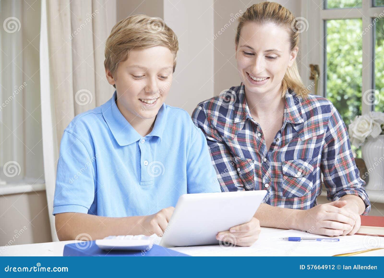 De vrouwelijke Studies die van Helping Boy With van de Huisprivé-leraar Digitale Tablet gebruiken