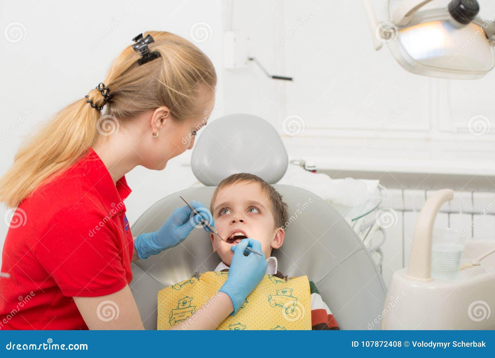 De vrouwelijke tandarts onderzoekt de tanden van het geduldige kind kindmond wijd open als tandarts` s voorzitter Close-up
