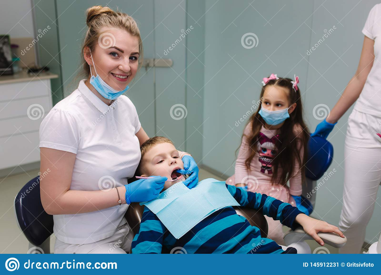 De vrouwelijke tandarts van de meisjehulp, nieuwe tanden examinationand behandeling van holten