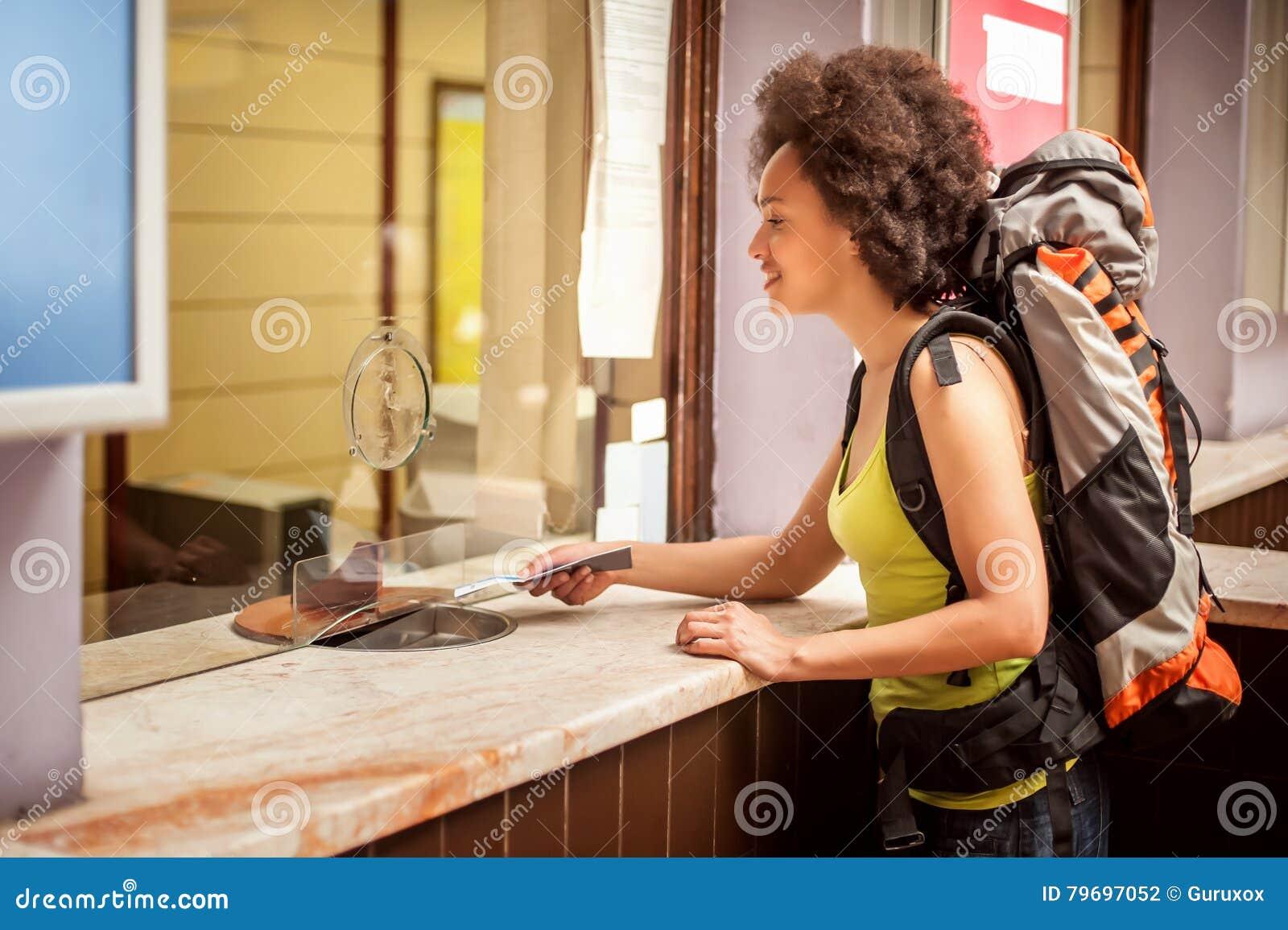 De vrouwelijke toerist koopt een kaartje bij de eindteller van het postkaartje