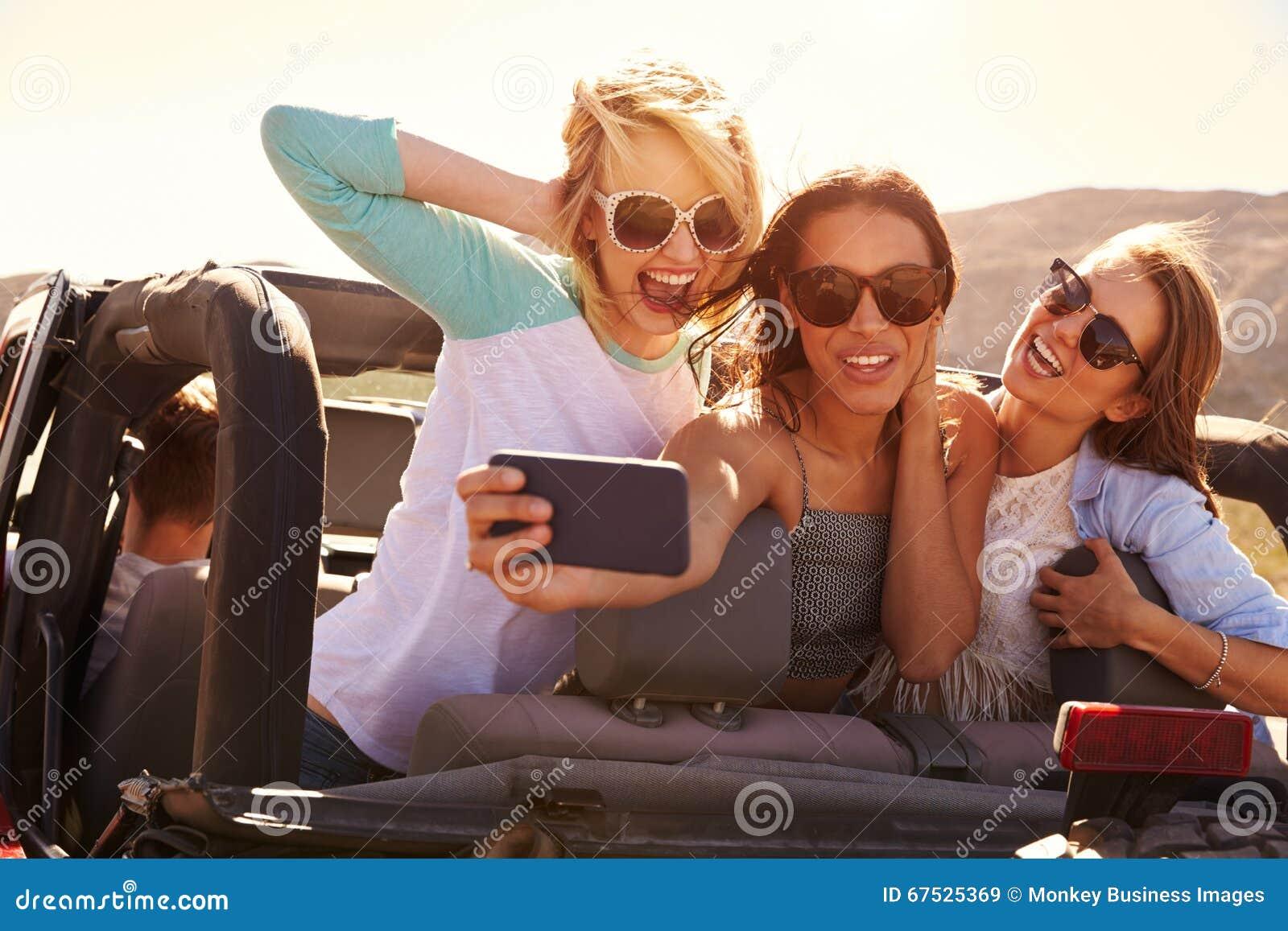 De vrouwelijke Vrienden op Weg halen in Convertibele Auto over die Selfie nemen
