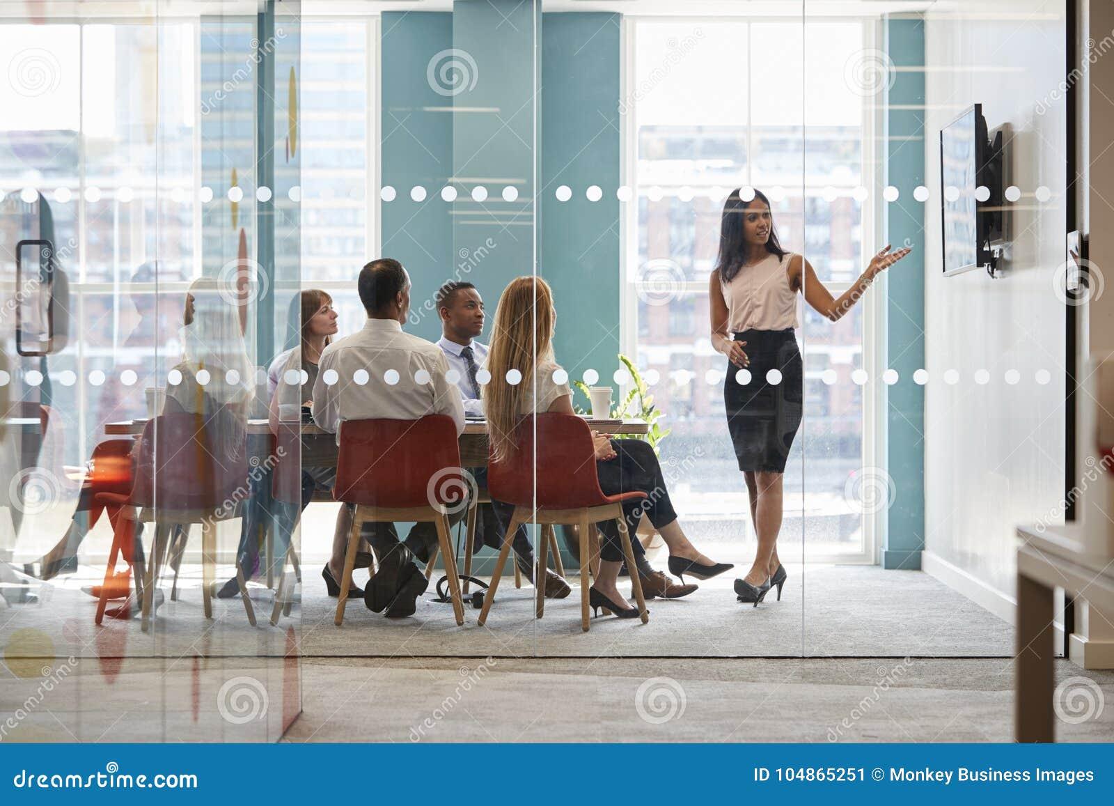 De vrouwelijke werkgever toont presentatie op het scherm op commerciële vergadering