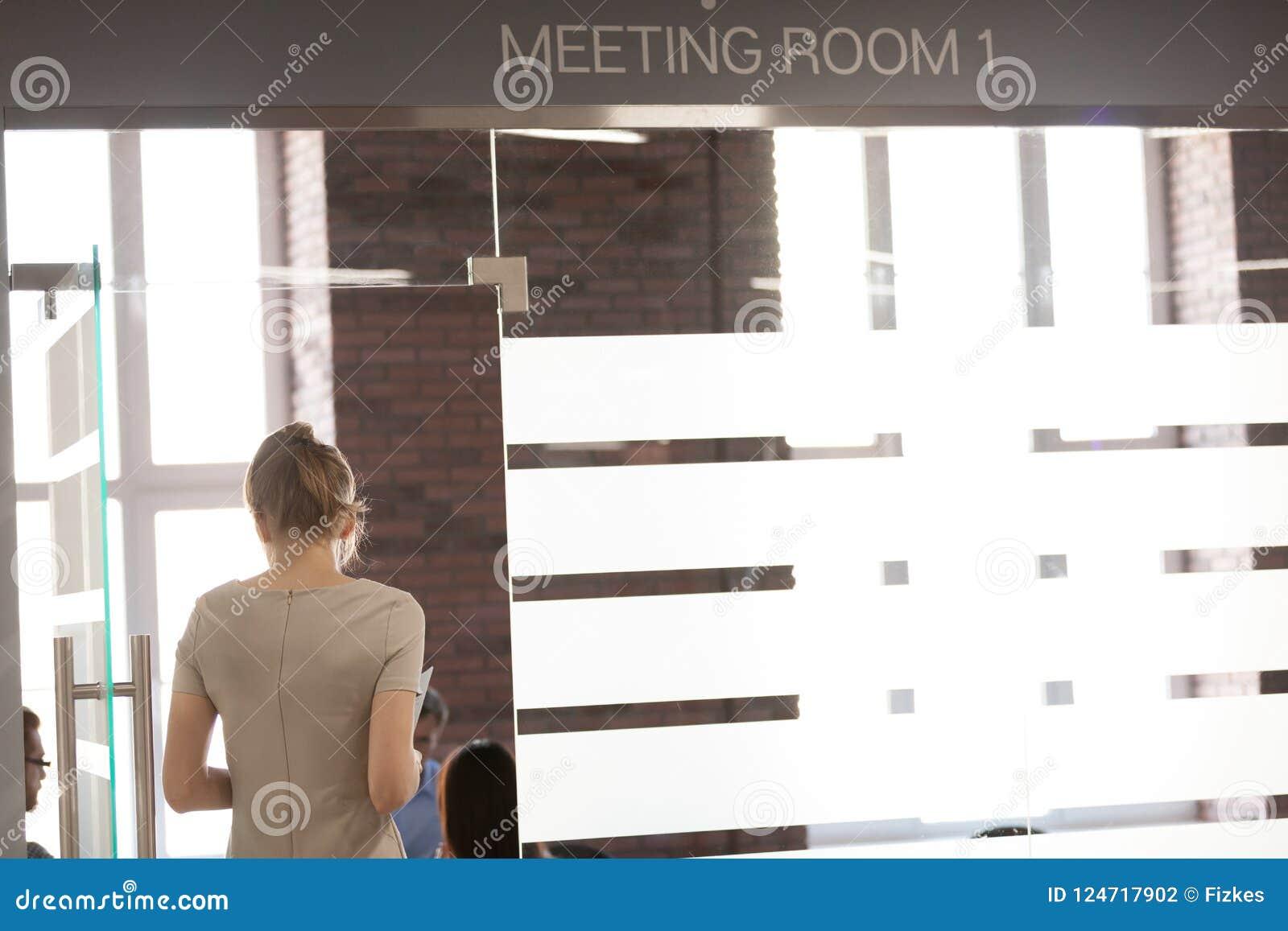 De vrouwelijke werknemer gaat vergaderzaal klaar voor presentatie in