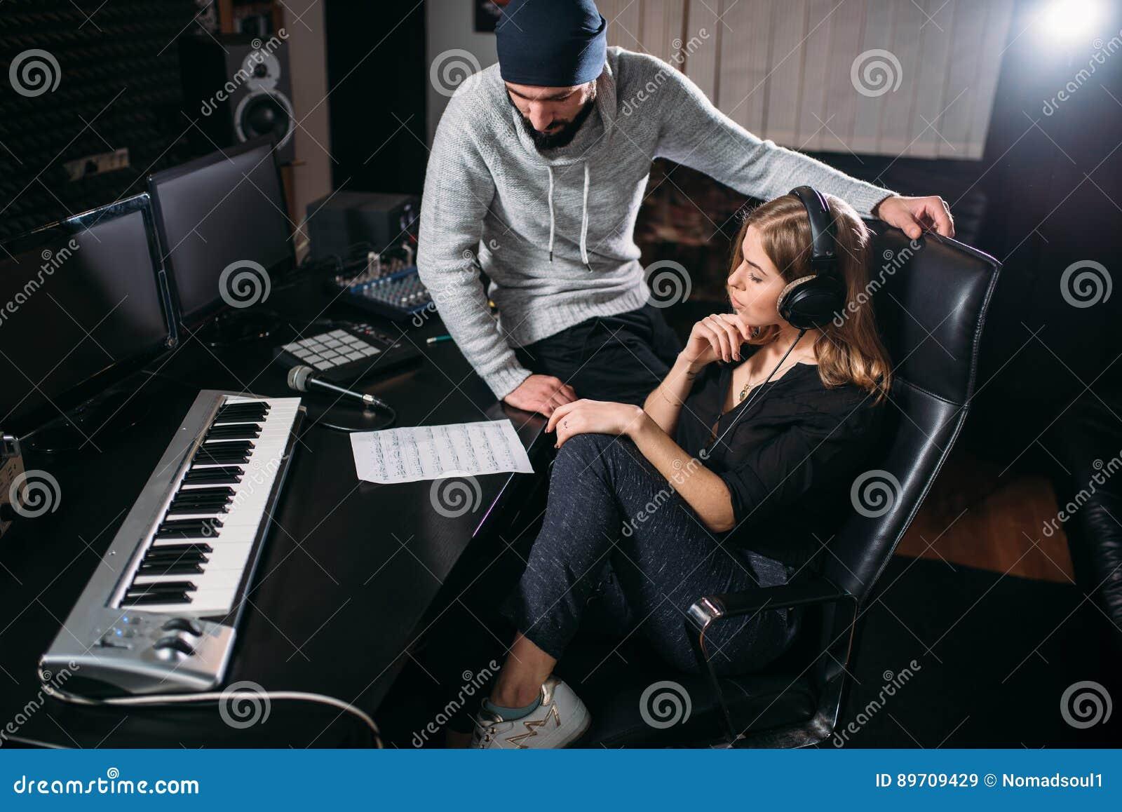 De vrouwelijke zanger luistert liedverslag in muziekstudio
