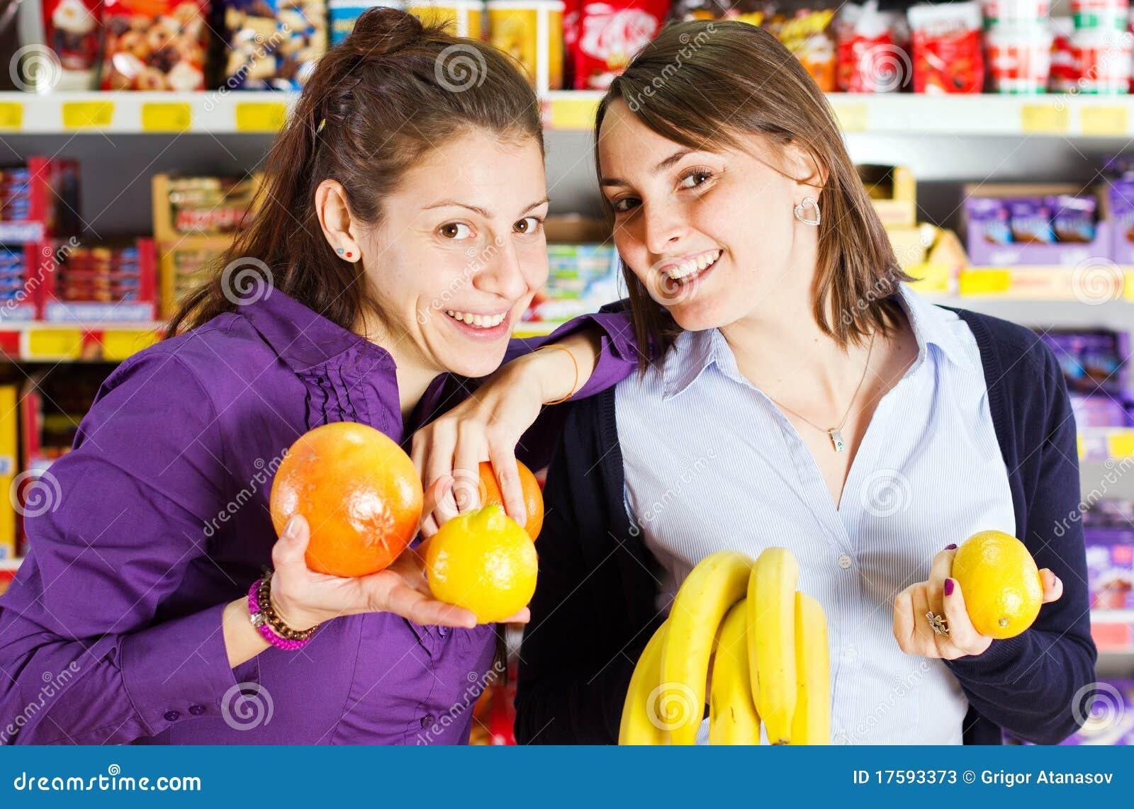 De vrouwen die in kruidenierswinkel winkelen slaan op