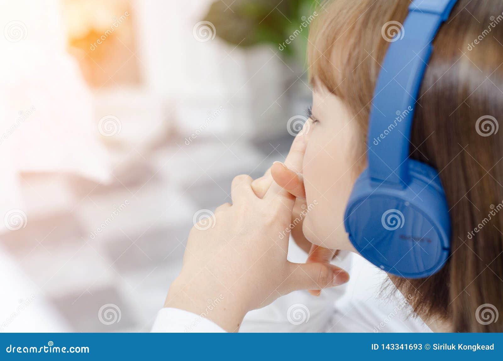 De vrouwen die oranje overhemden dragen luisteren aan muziek en zijn gelukkig