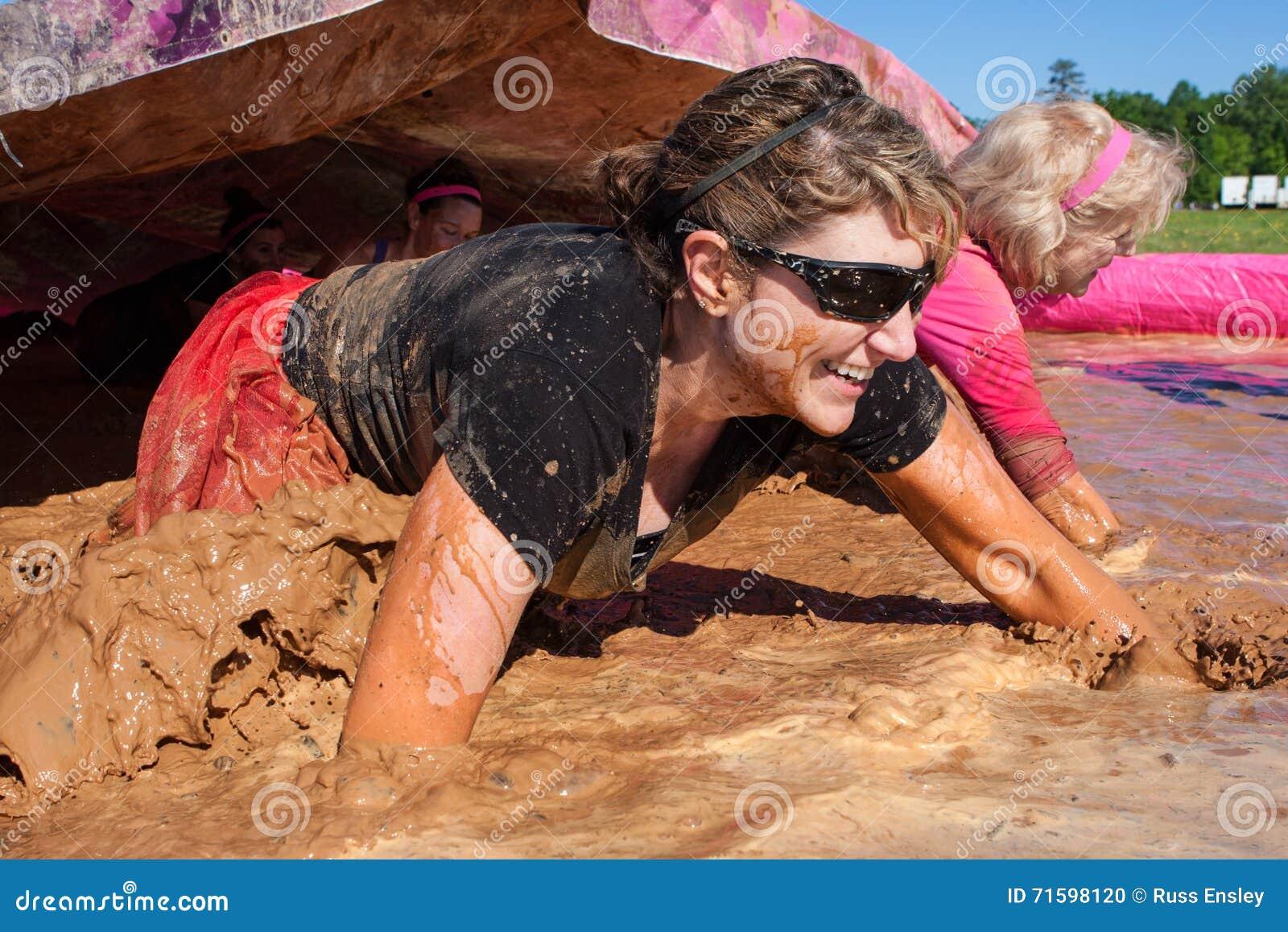 De vrouwen kruipen door Muddy Water At Dirty Girl-Modderlooppas