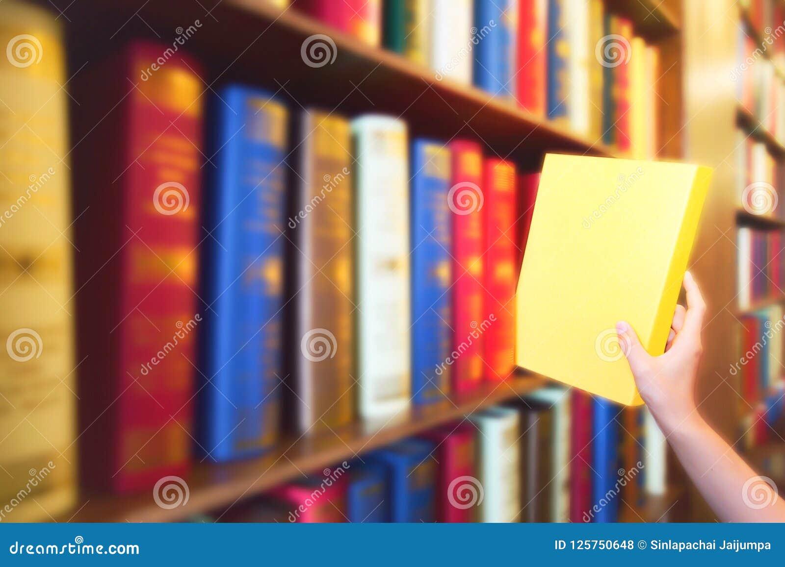 De vrouwen overhandigen het trekken van geel boek van houten boekenrekken in openbare bibliotheek Kleurrijke boeken, Handboek, Li