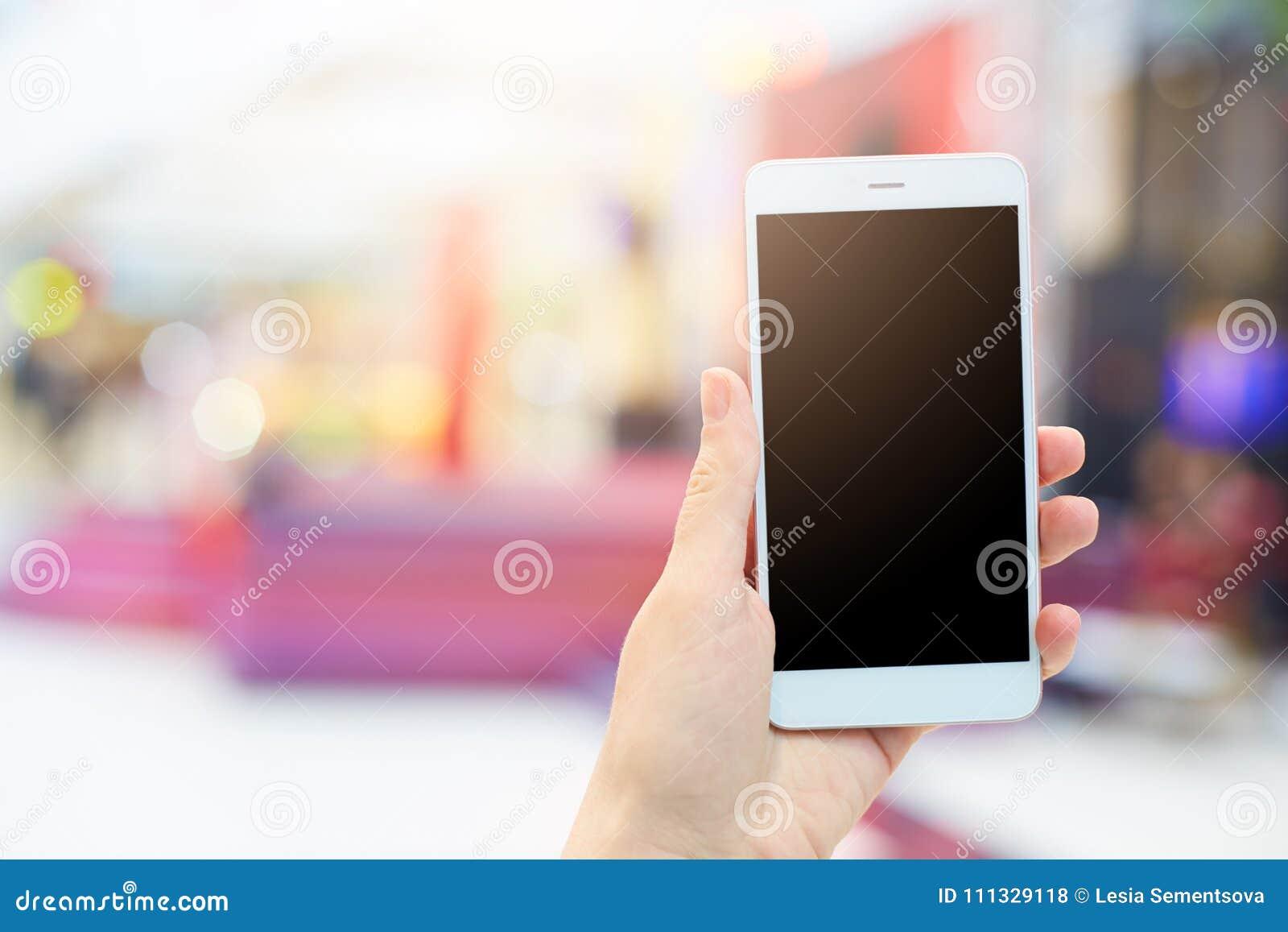 De vrouwen` s handen houdt modern elektronisch gadget Onherkenbaar wijfje met witte mobiele telefoon en het lege zwarte scherm vo