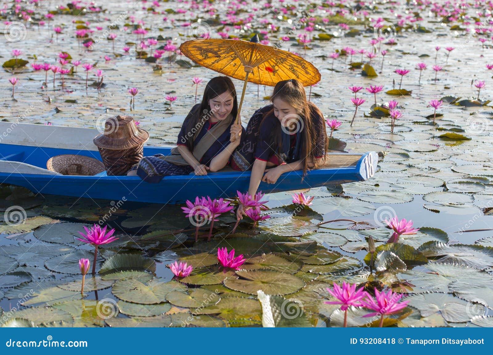 De vrouwen van Laos in het meer van de bloemlotusbloem, Vrouw die traditionele Thaise mensen, Rode Lotus Sea UdonThani Thailand d