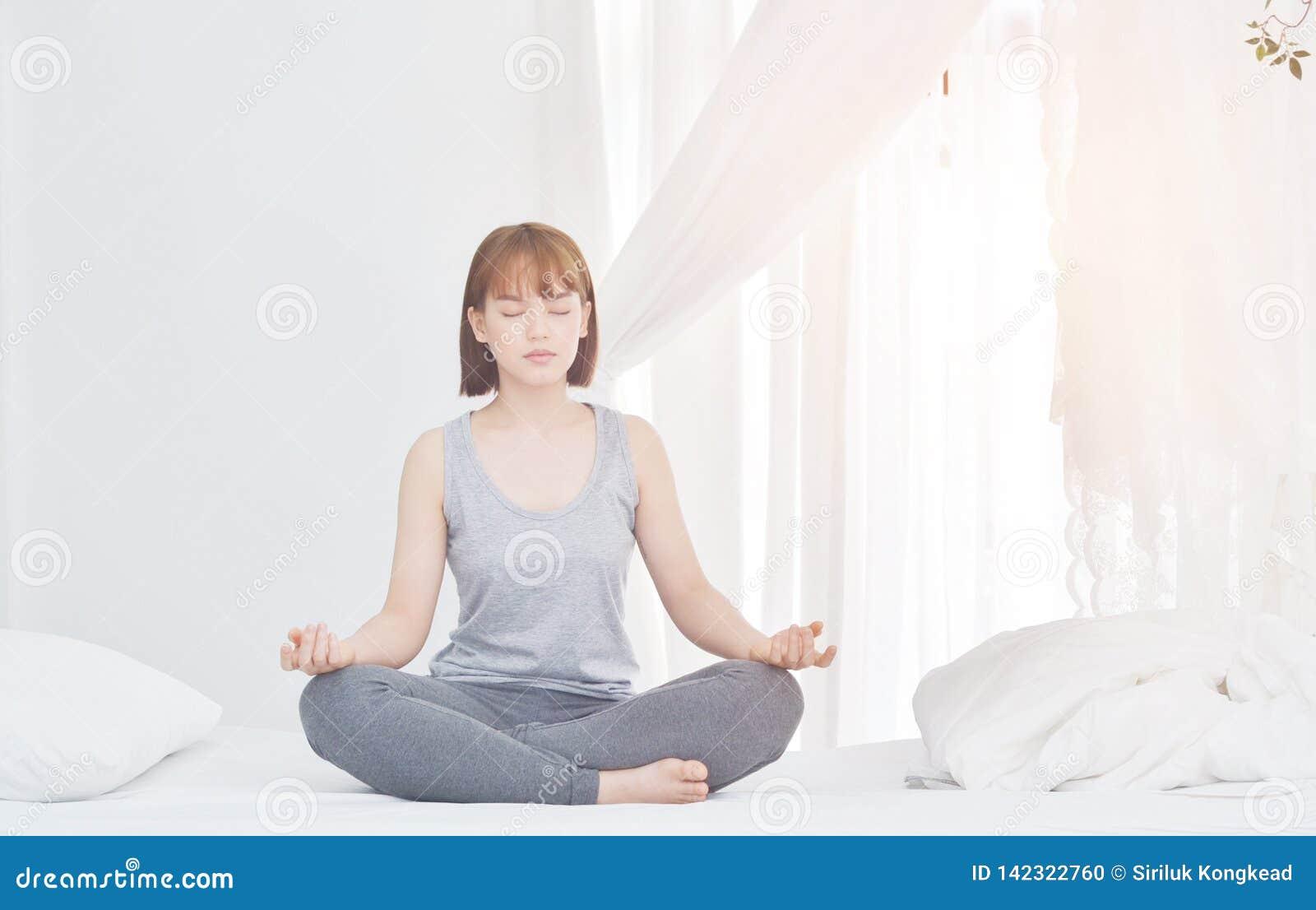 De vrouwen zitten op yoga op de matras