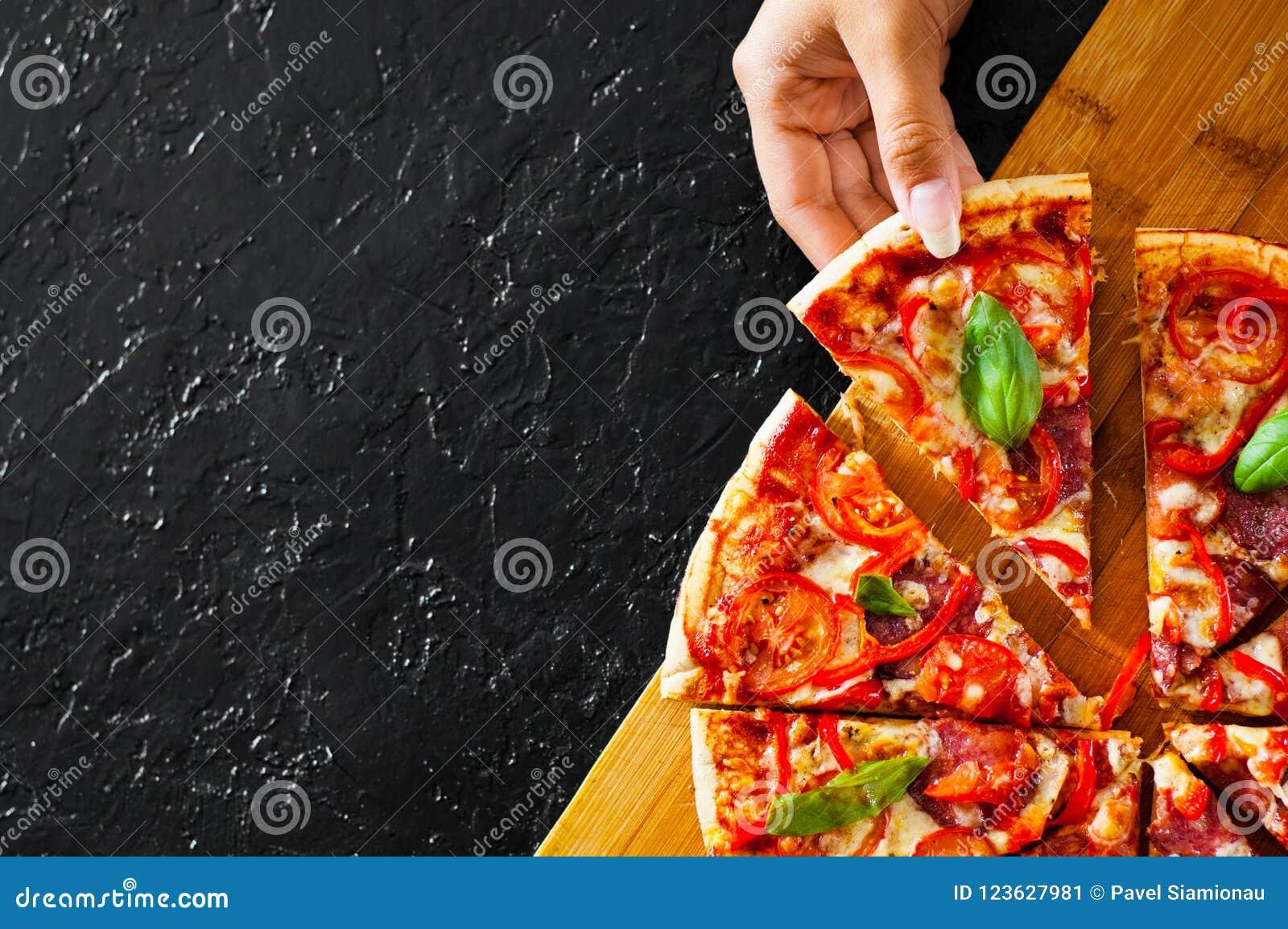 De vrouwenhand neemt een stuk van Pizza met Mozarellakaas, Ham, Tomaten, salami, peper, pepperonis, Kruiden en Vers Basilicum Ita