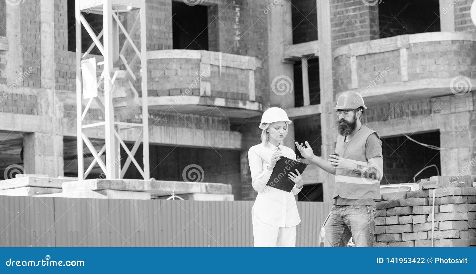 De de vrouweningenieur en bouwer communiceren bij bouwwerf Communicatie van het bouwteam concept verhoudingen